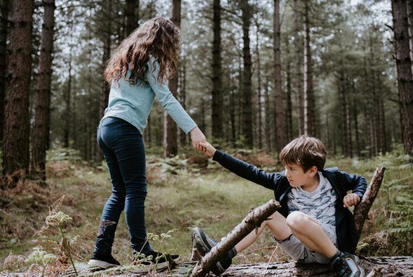 boy and girl playing on three tree log