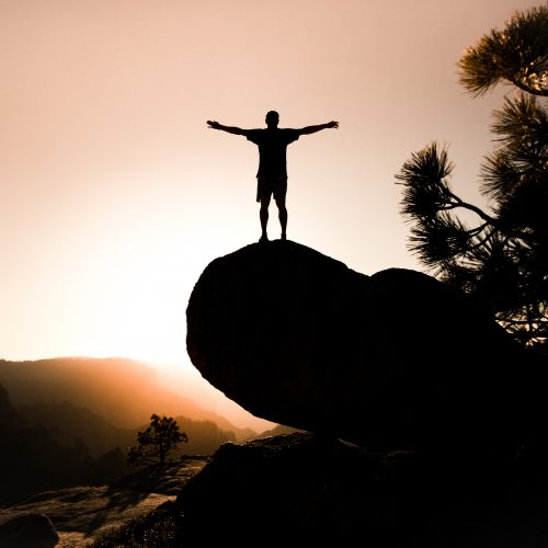 silhouette of person on rock
