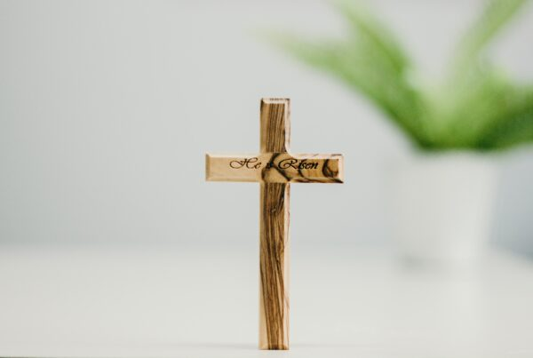 brown wooden cross with green leaves
