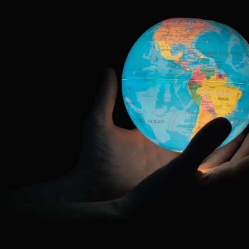 blue and brown globe on persons hand